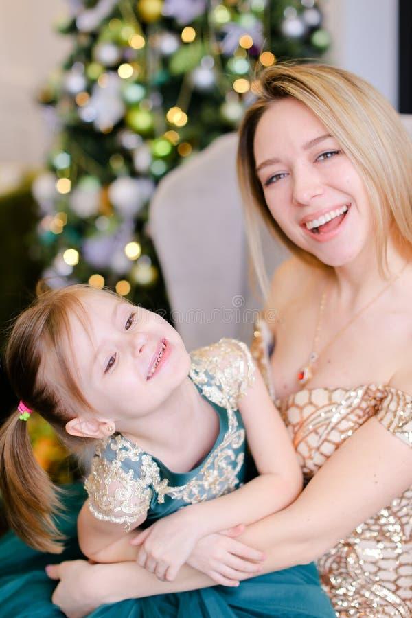 Belle mère heureuse s'asseyant avec la robe de port de petite fille près de l'arbre de Noël photos libres de droits