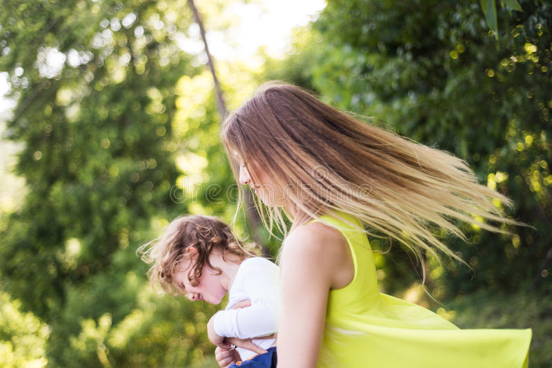 Belle mère tournant son fils Nature ensoleillée d'été photo stock