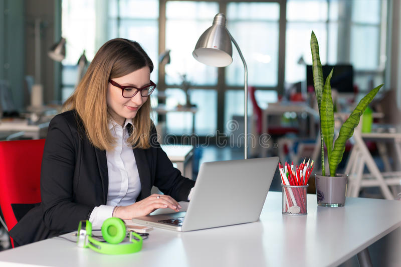 Belle Madame d'affaires dans l'habillement officiel travaillant sur l'ordinateur portable photos libres de droits