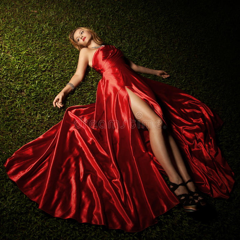 Belle Madame In Red Dress se trouvant sur l'herbe verte photographie stock