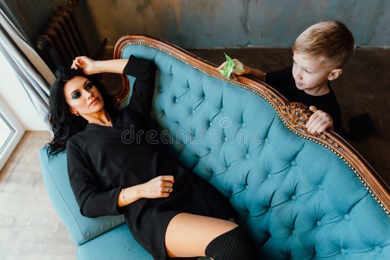Belle maman de brune étreignant son fils se trouvant sur le sofa famille mère et son garçon mignon Vêtements noirs photos libres de droits