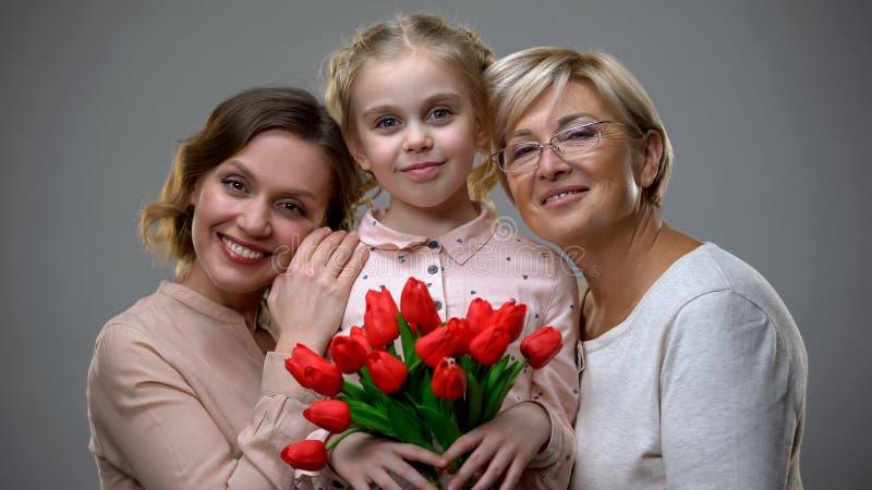 Belle mamie et m?re ?treignant la fille avec des tulipes dans des mains, g?n?rations photographie stock
