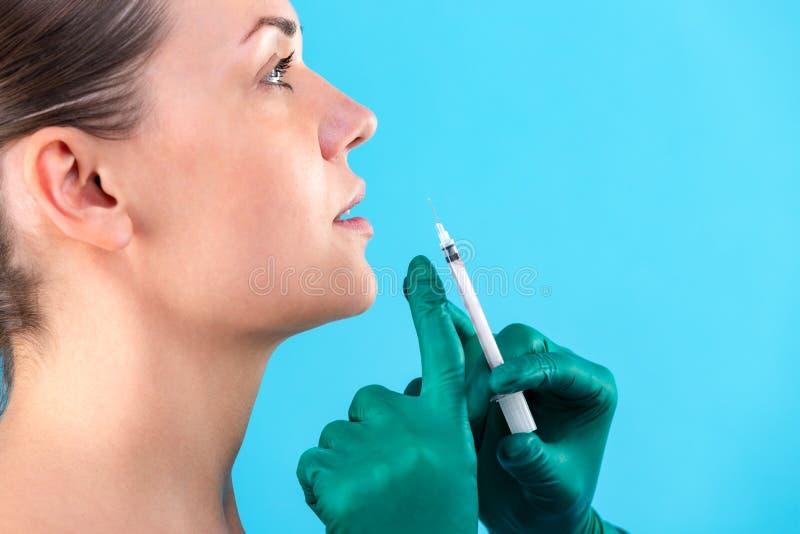 Belle mani del fronte e dell'estetista della donna con la siringa Medico fa l'iniezione cosmetica nel labbro superiore Pulisca la immagini stock libere da diritti