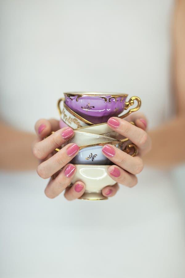 Belle mani della donna con smalto rosa perfetto che tiene poche tazze di tè d'annata fotografia stock