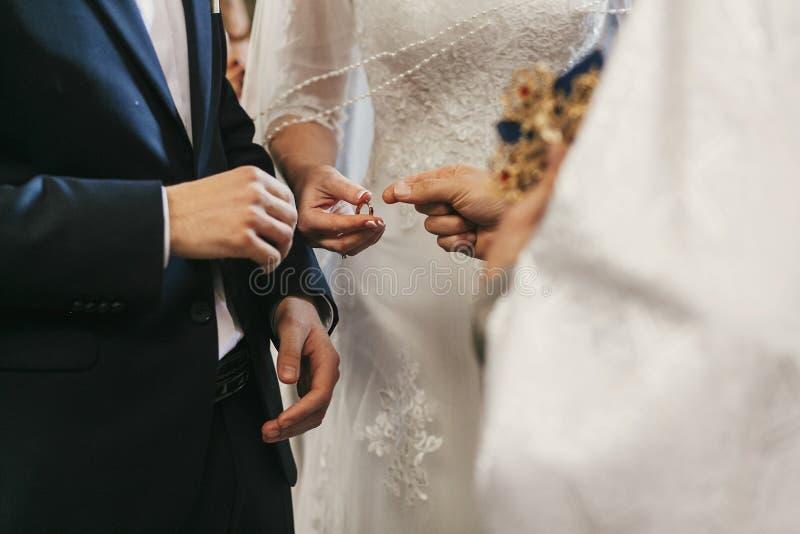 Belle mani dello sposo e della sposa che scambiano le fedi nuziali nel chur fotografia stock libera da diritti