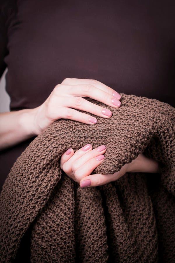 Belle mani femminili che tengono maglione tricottato marrone Manicure con smalto rosa Concetto accogliente fotografia stock
