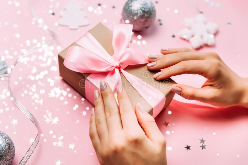 Belle mani femminili con il contenitore di regalo d'avanguardia della tenuta del manicure sul fondo festivo di natale immagini stock libere da diritti