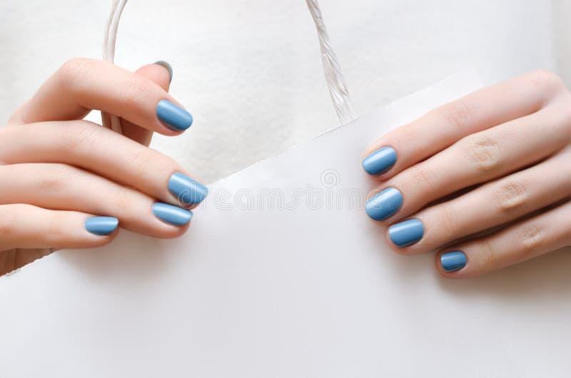 Belle mani femminili con il manicure blu fotografie stock