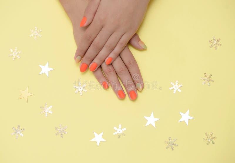 Belle mani femminili con il manicure luminoso su un fondo colorato immagini stock libere da diritti