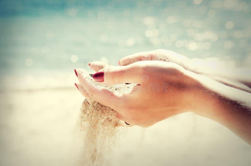 Belle mani femminili e la sabbia sui precedenti del mare immagine stock libera da diritti