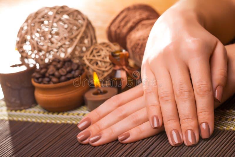 Belle manucure brune sur un fond en bambou photo stock