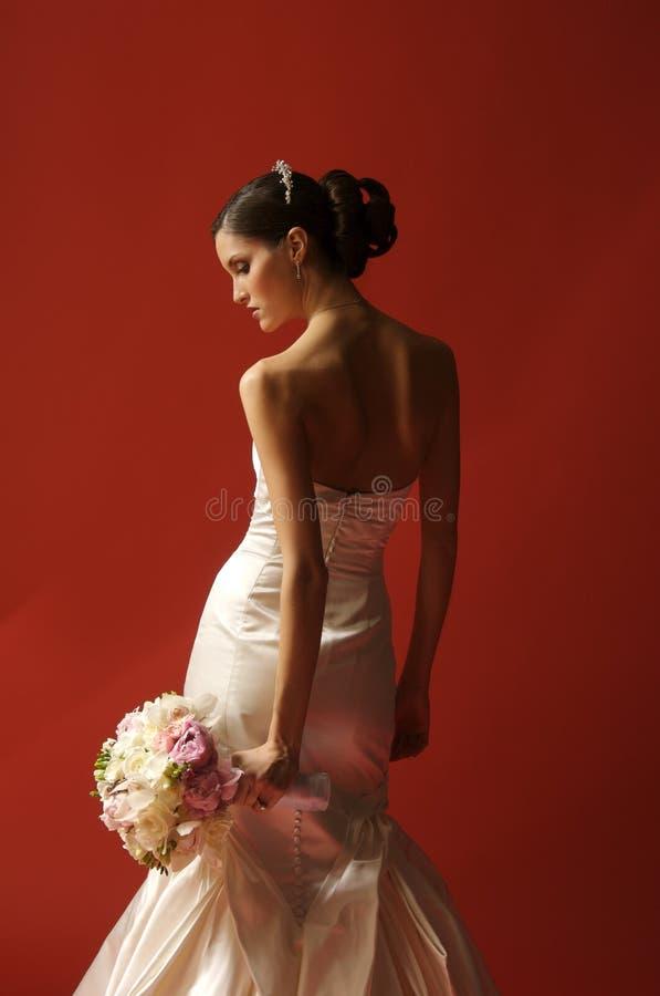Belle mariée avec le bouquet sur le fond rouge image libre de droits