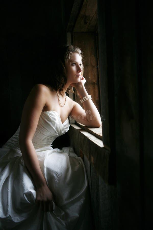 Belle mariée regardant hors de l'hublot images stock