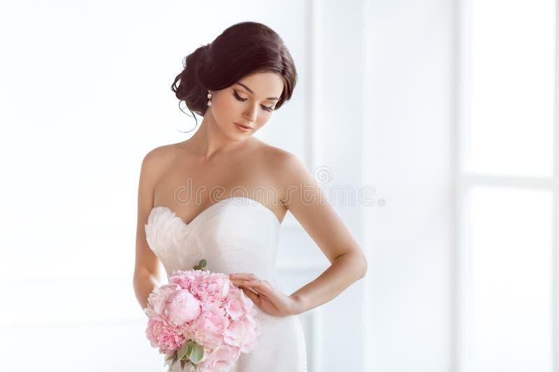 Belle mariée Robe de mode de maquillage de coiffure de mariage et bouquet de luxe des fleurs photos stock