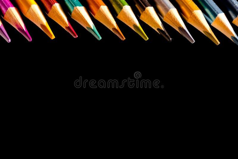 Belle matite nere e colorate messe dell'matite colorate su fondo nero Presto alla scuola Di nuovo al banco fotografia stock libera da diritti
