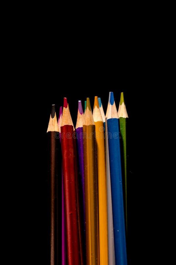 Belle matite nere e colorate messe delle matite colorate su fondo nero Presto alla scuola Di nuovo al banco fotografia stock libera da diritti