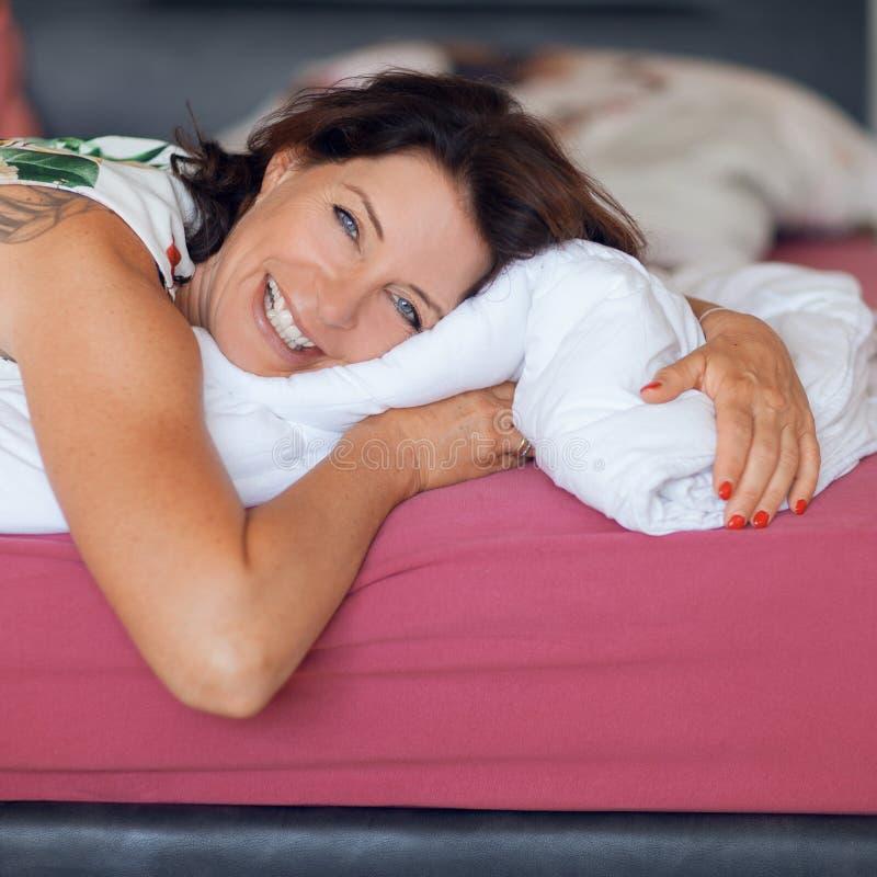 Belle meilleure femme d'âge se trouvant sur la détente de lit, appréciant la vie photographie stock