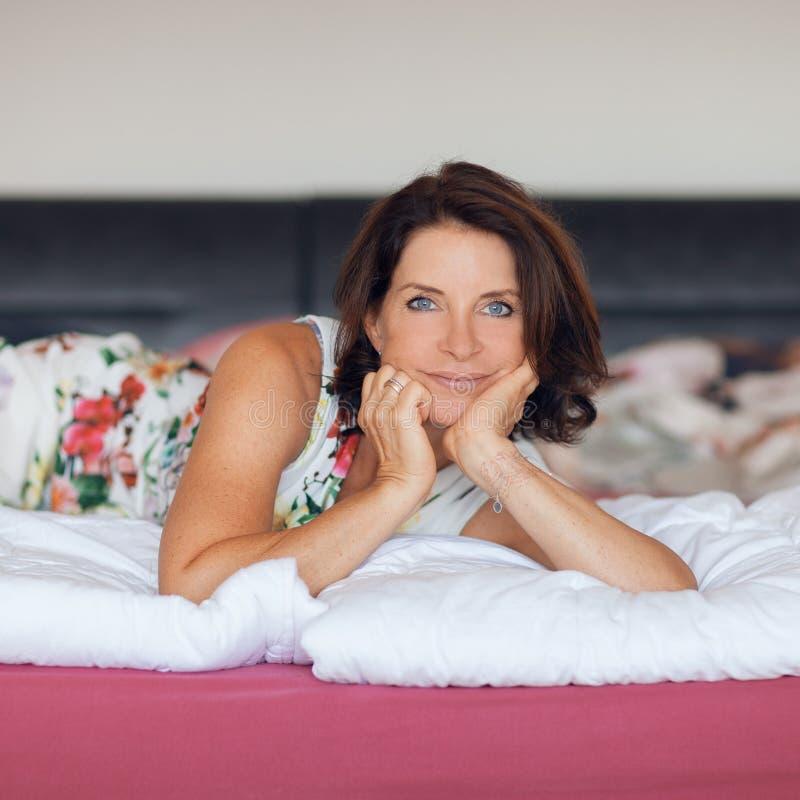 Belle meilleure femme d'âge se trouvant sur la détente de lit, appréciant la vie image stock