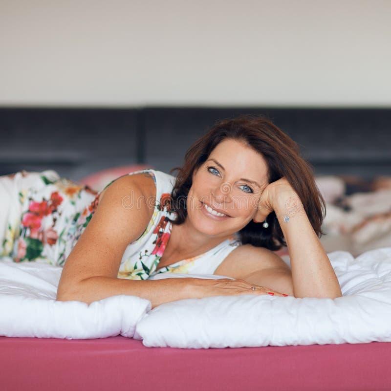 Belle meilleure femme d'âge se trouvant sur la détente de lit, appréciant la vie photos stock