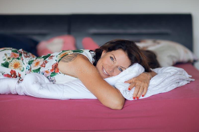 Belle meilleure femme d'âge se trouvant sur la détente de lit, appréciant la vie photo libre de droits