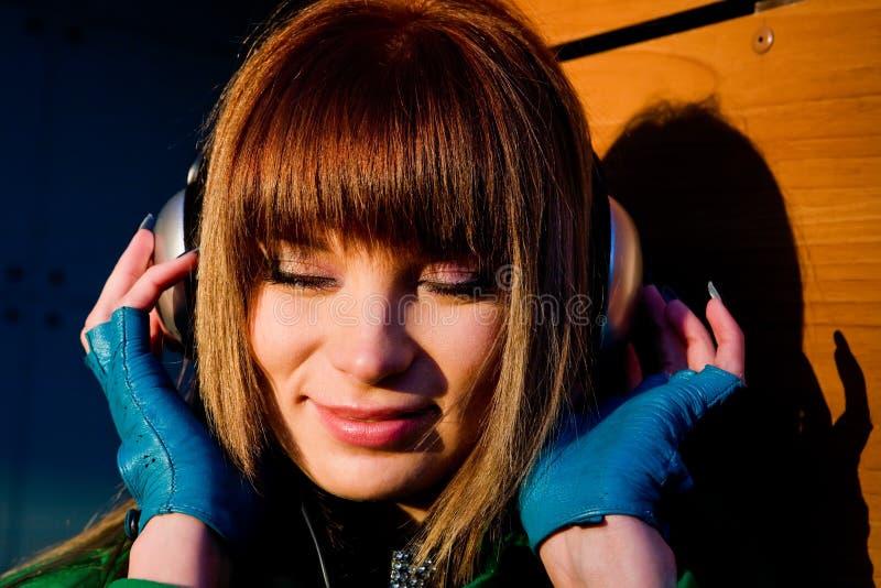 Belle musique de écoute de jeune femme dans des écouteurs photo stock
