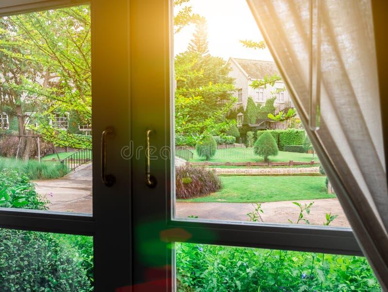 Belle nature de jardin derrière la fusée d'éclairage de fenêtre lumineuse pendant le matin Cadre blanc et poignée foncée Regardez image libre de droits