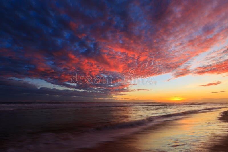 Belle nuvole colorate alla spiaggia al tramonto immagine stock libera da diritti