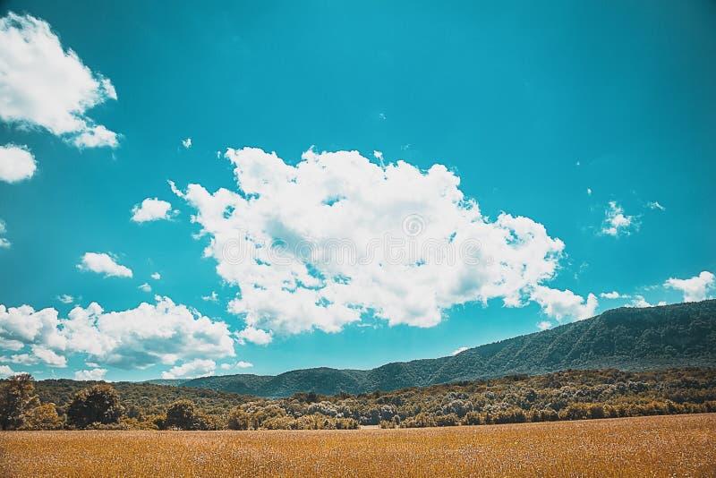 Belle nuvole su un cielo blu con struttura delle montagne e del campo in priorità alta fotografie stock libere da diritti