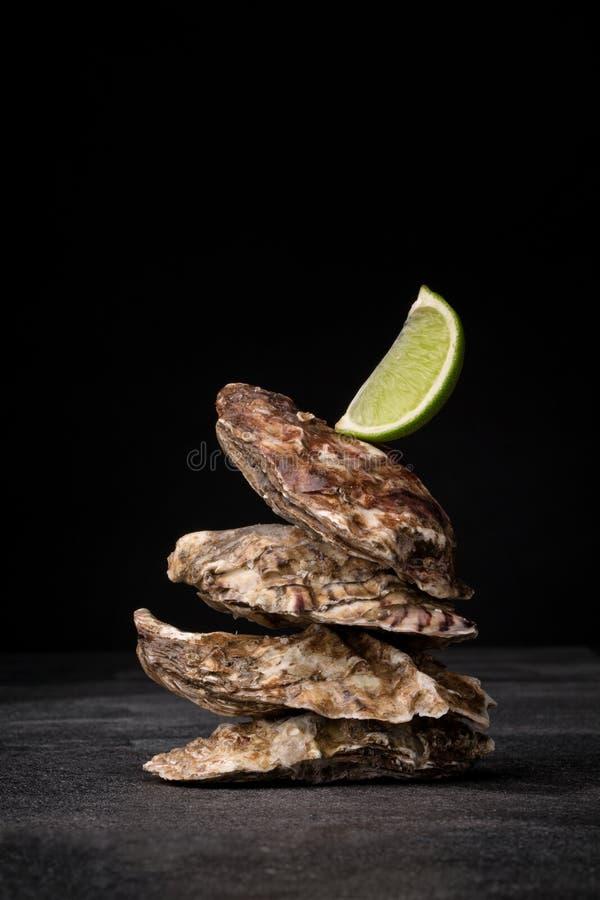 Belle ostriche chiuse su un fondo nero Molluschi appetitosi del mare con calce succosa Ingredienti marini costosi fotografie stock