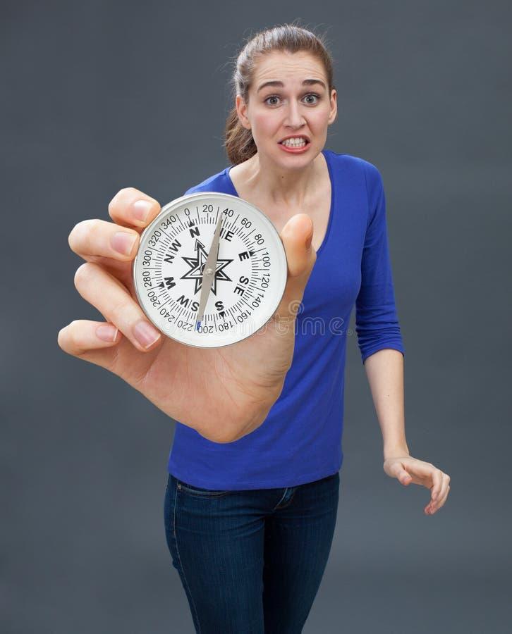 Belle panique soucieuse de jeune femme, tenant une grande boussole images stock