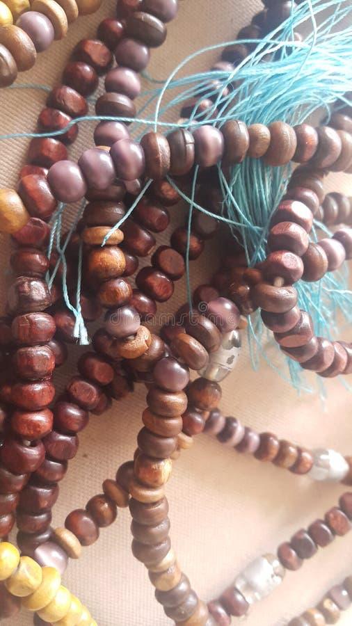 Belle perle di preghiera o rosario di legno disposto sopra il fondo del tessuto immagine stock