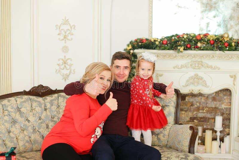 Belle personne enceinte de feamle s'asseyant avec l'homme et la fille près de l'arbre de Noël et de la cheminée décorée photo libre de droits