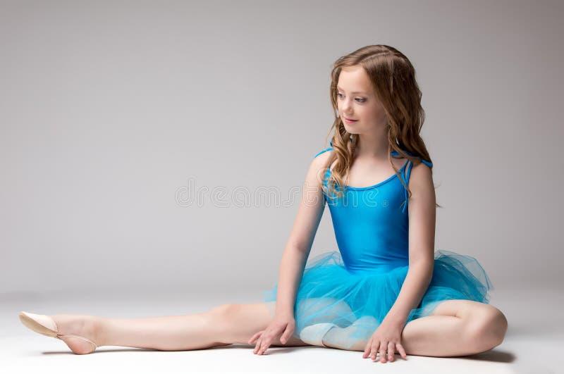 Belle petite ballerine posant faisant l'étirage photos libres de droits