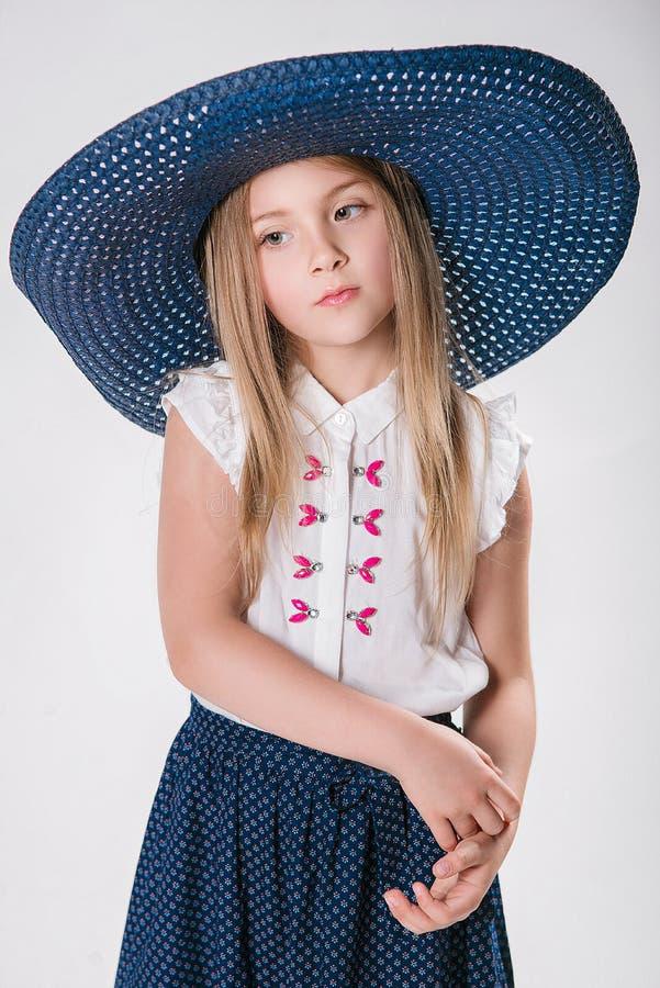 Belle petite fille à la mode avec les cheveux blonds dans un chapeau avec le bord large et une longue jupe à la mode dans le stud photographie stock