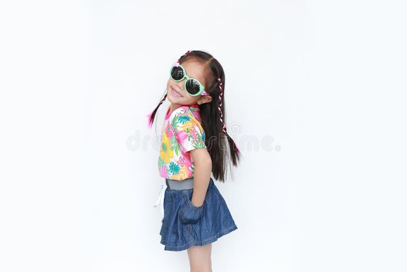 Belle petite fille asiatique d'enfant utilisant une robe et des lunettes de soleil d'été de fleurs d'isolement sur le fond blanc  photographie stock libre de droits