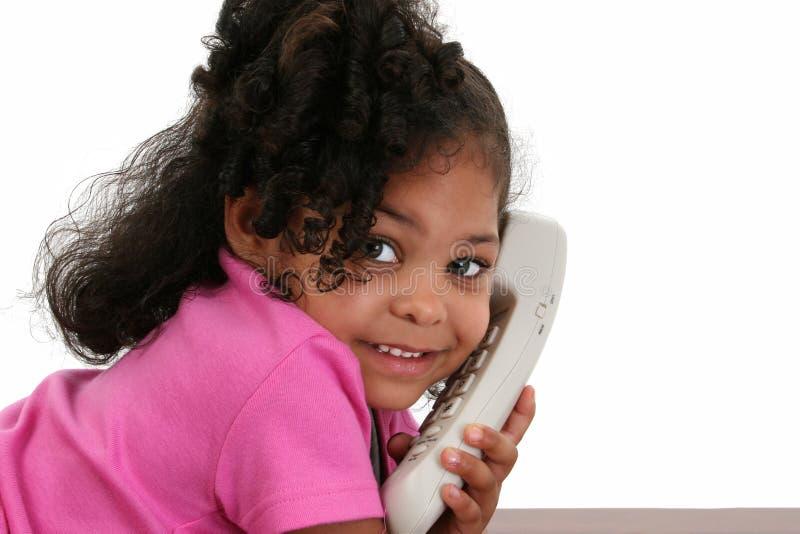 Belle petite fille au téléphone image stock