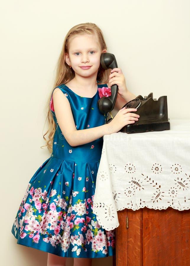 Belle petite fille avec de longs cheveux blonds, prises l'oreille de l' photographie stock