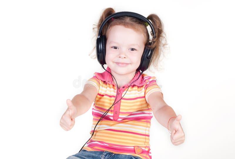 Belle petite fille avec des écouteurs montrant des pouces  image libre de droits