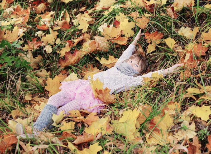 Belle petite fille avec des feuilles d'érable image libre de droits