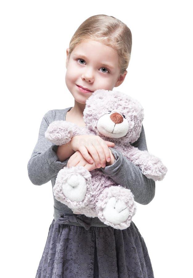 Belle petite fille avec l'ours de nounours d'isolement image stock