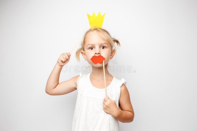 Belle petite fille avec la couronne de papier et les lèvres rouges posant sur le fond blanc à la maison photographie stock