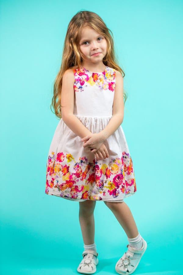 Belle petite fille avec la longue position de cheveux blonds sur un fond bleu photo stock
