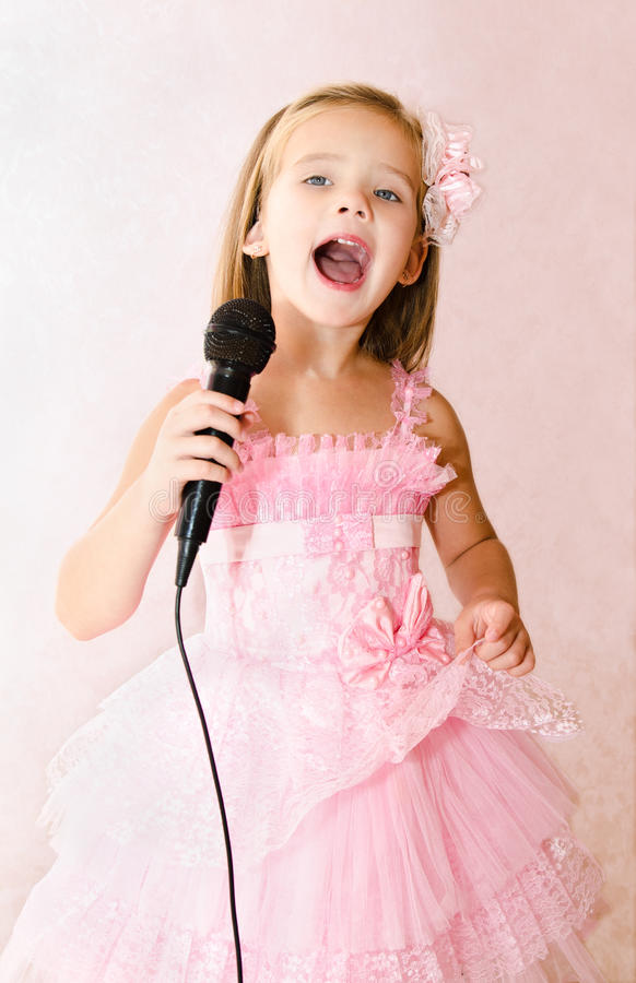 Belle petite fille avec le microphone dans la robe de princesse photo stock
