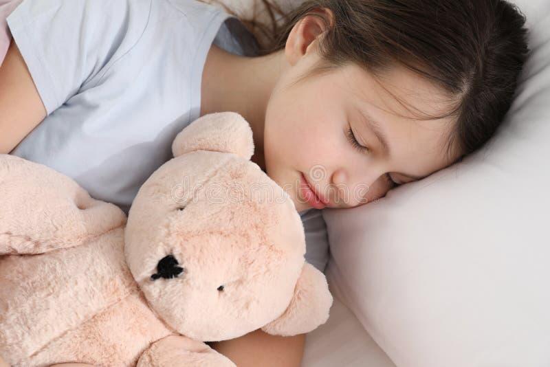 Belle petite fille avec le sommeil d'ours de nounours image libre de droits