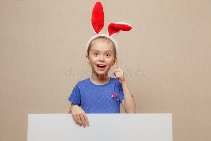 Belle petite fille avec les oreilles de lapin et la bannière vide Joyeuses Pâques photo libre de droits