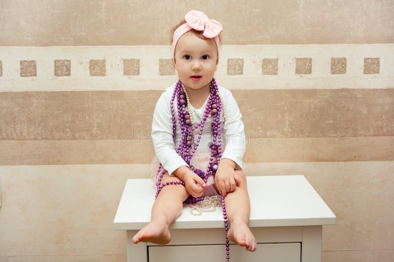 Belle petite fille avec un arc rose et des perles pourpres images libres de droits