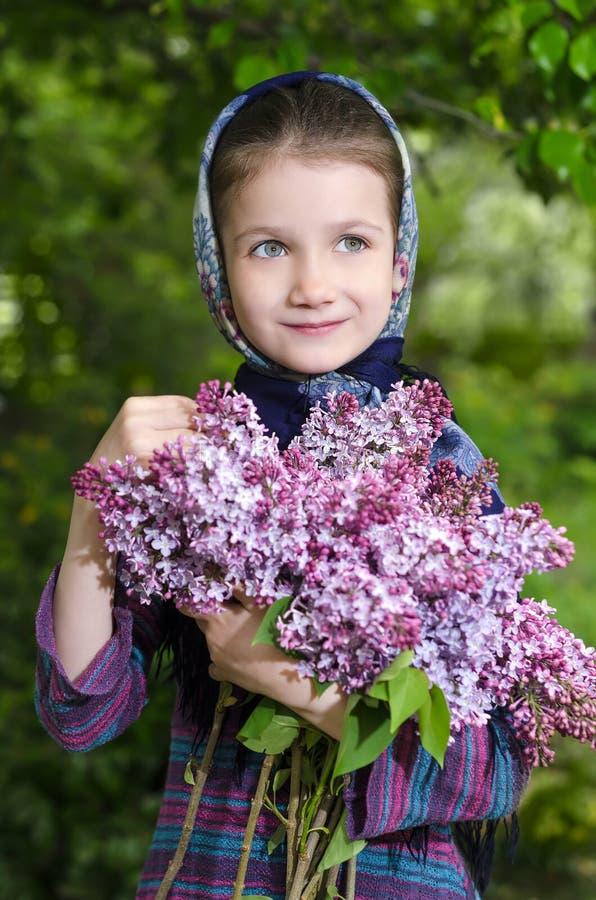 Belle petite fille avec un bouquet d'un lilas de floraison à disposition image stock