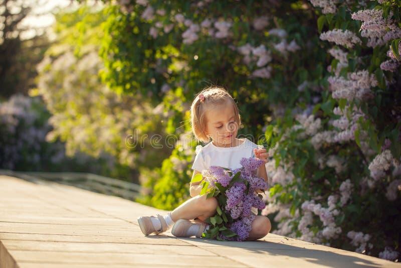 Belle petite fille avec un bouquet des lilas au printemps photos stock