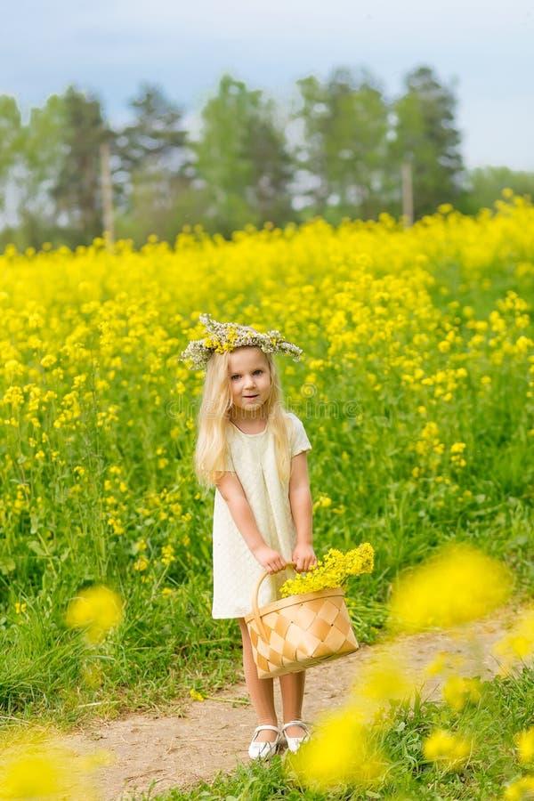 Belle petite fille avec une guirlande sur sa tête jouant dans un flo image libre de droits