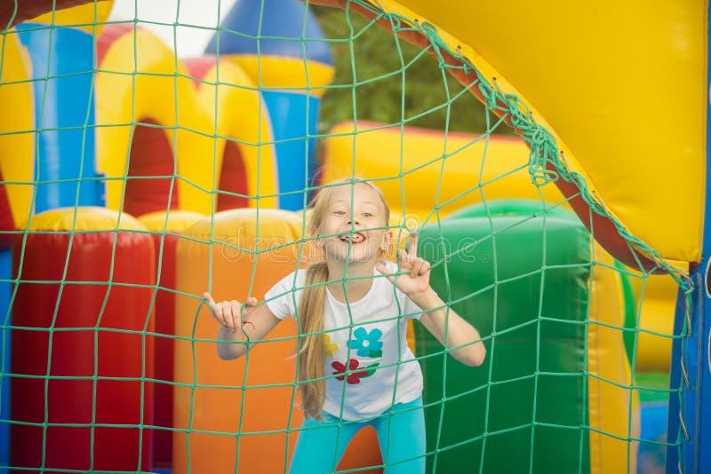 Belle petite fille ayant l'amusement jetant un coup d'oeil par derrière le trempoline gonflable de maille photos stock